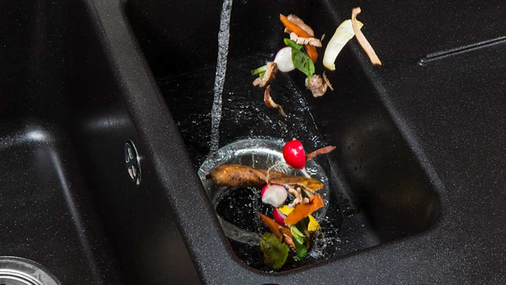 food being dropped down a garbage disposal with the water running