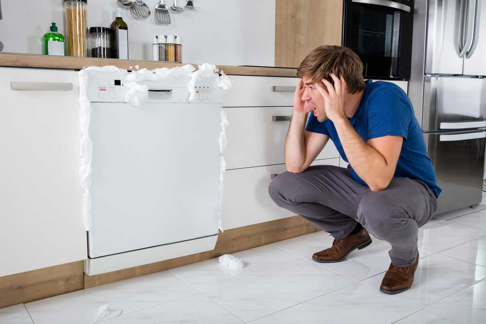 frustrated man kneeling next to dishwasher with suds coming out of the seams