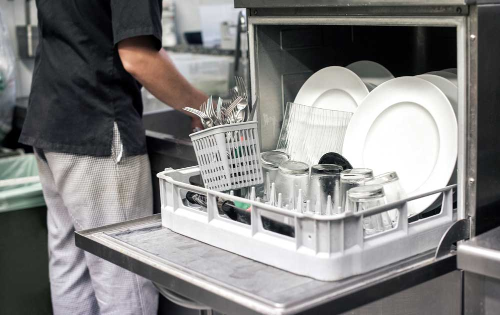 open dish washer with clean dishes and someone working at sink in background