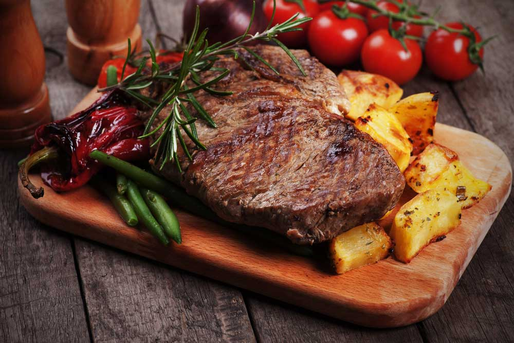 Steak and potatoes on cutting board surrounded by vegetable