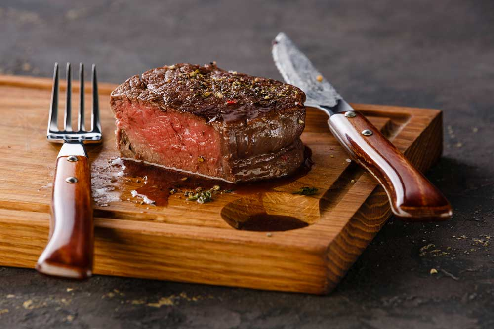 Filet mignon cut on a cutting board with a knife