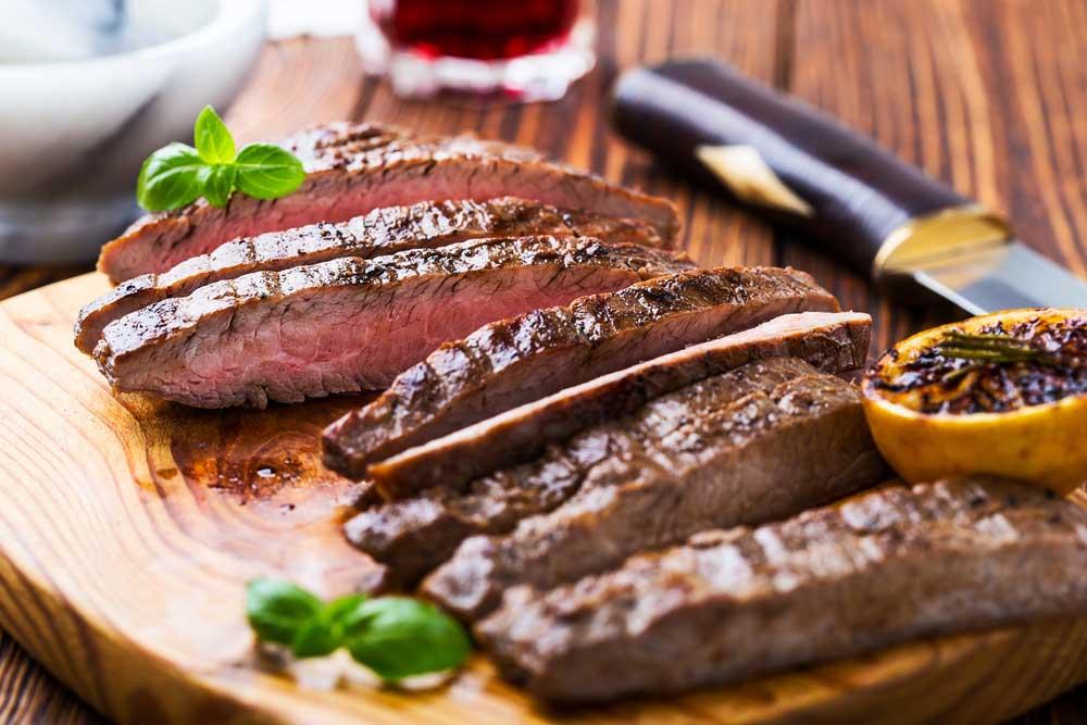 sliced medium rare flank steak on a cutting board