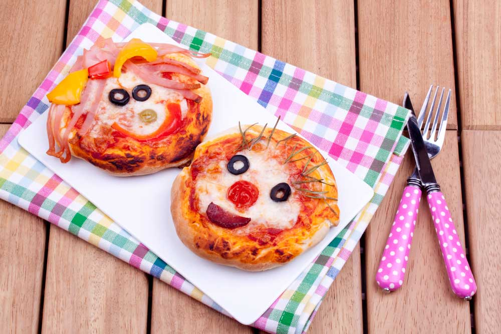 2 small pizzas decorated with smiley faces