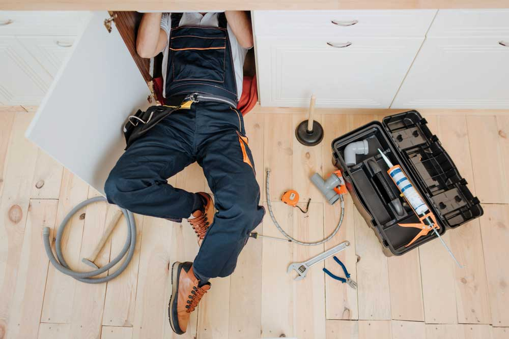 person under sink surrounded by tools