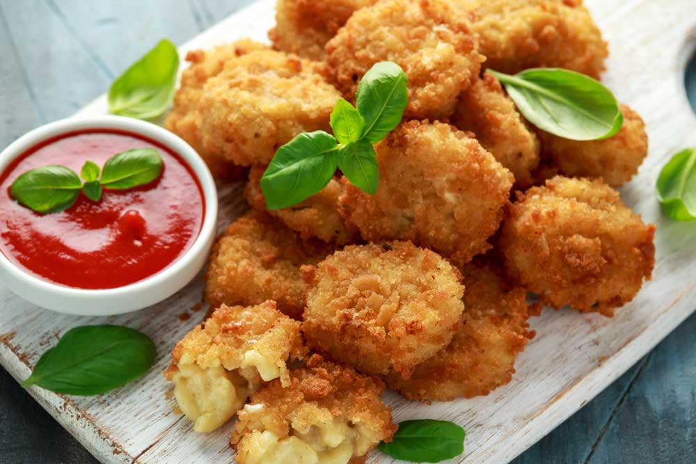 mac and cheese bites garnished with basil and a small bowl of ketchup