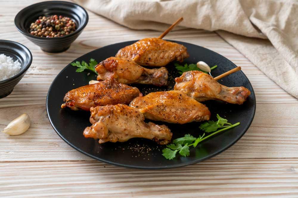 seasoned Chicken wings on scewers on a black plate