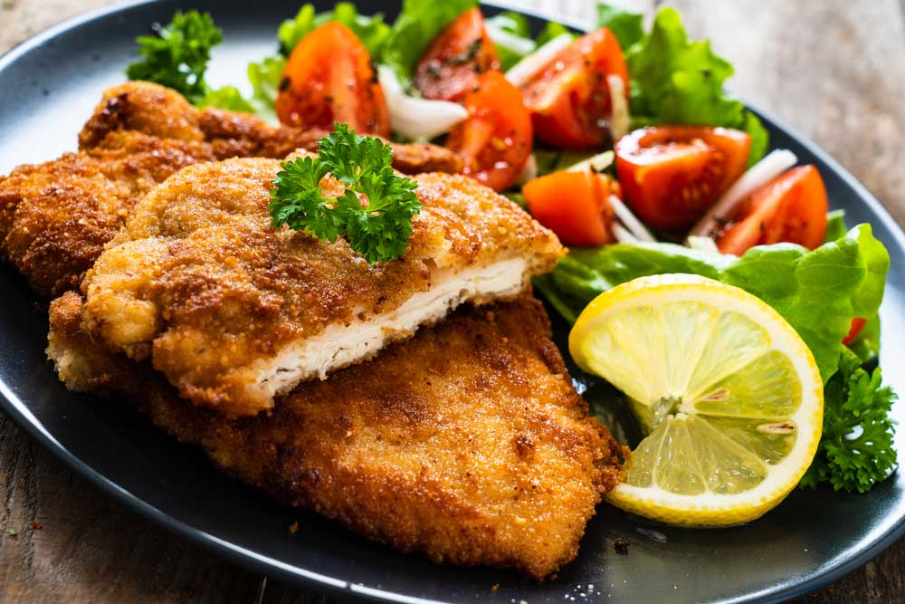 Breaded pork chops on a plate with salad and garnish
