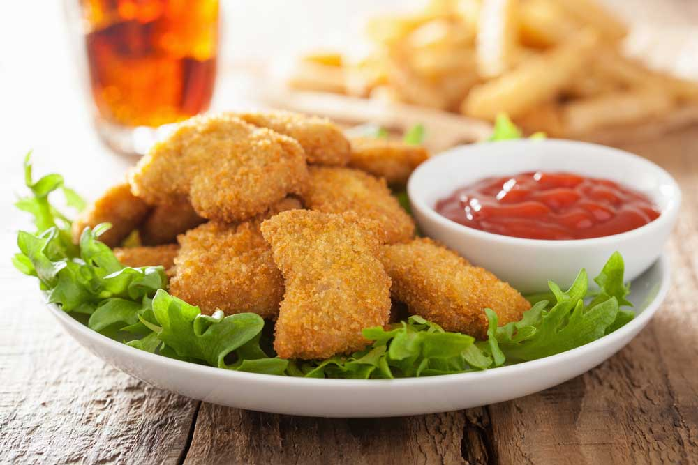 chicken nuggets on plate with small bowl of ketchup