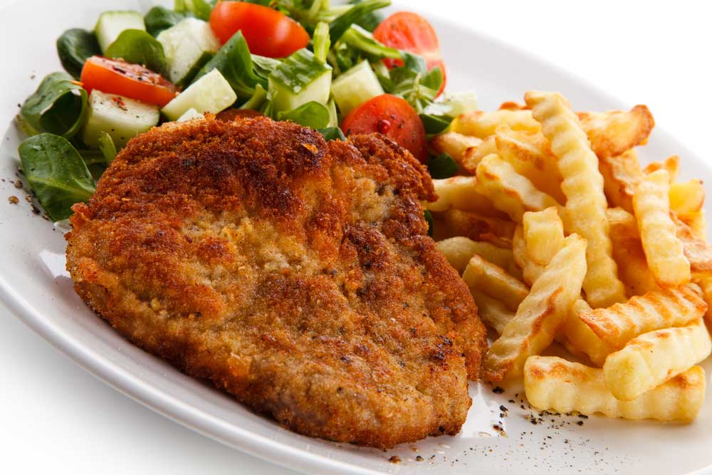 Breaded pork chop on a white plate with fries and salad