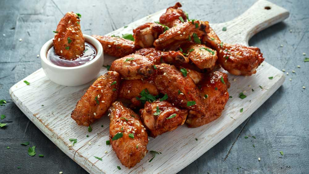 Sauced chicken wings displayed on a on a cutting board