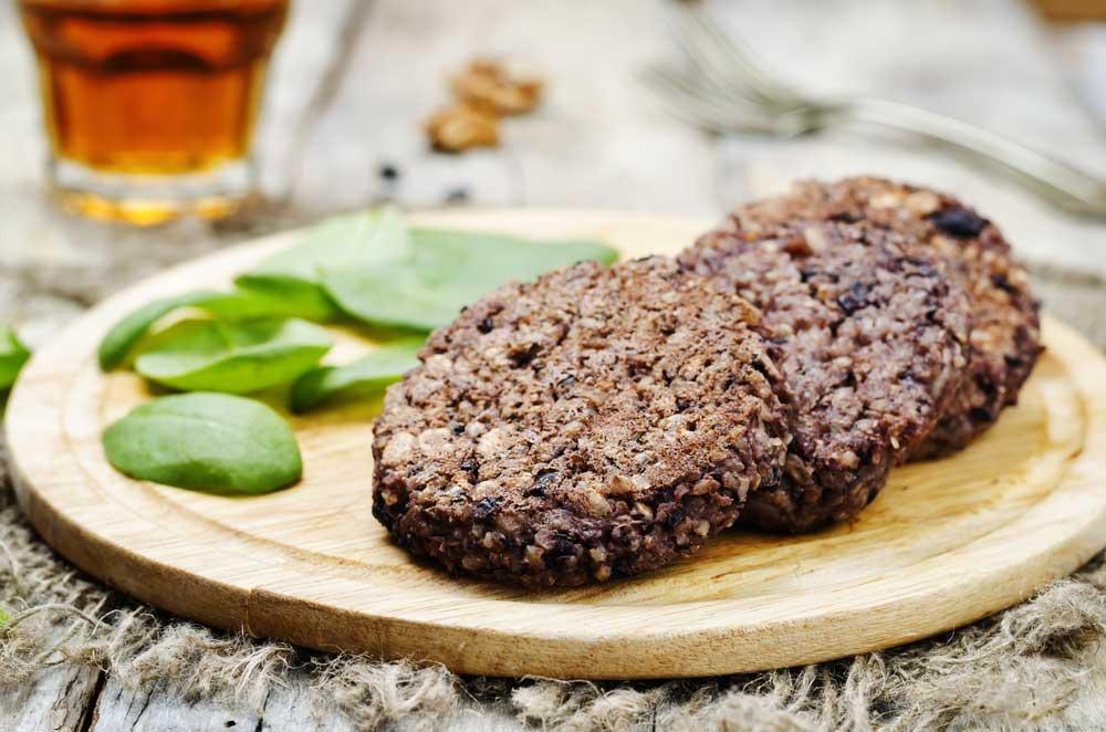 Black bean burger patties on a wooden plate