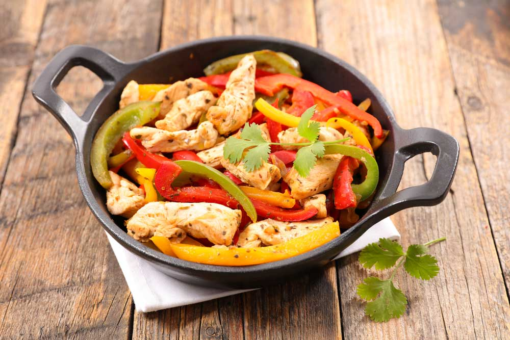 chicken and peppers in an cast iron dish on a wooden table