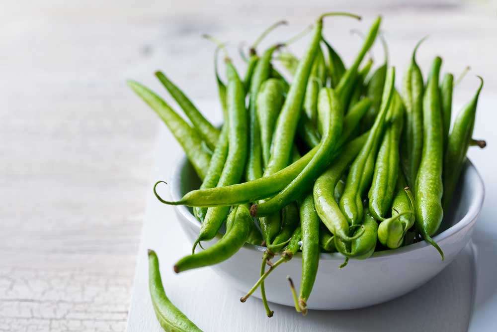 fresh green beans in a white bowl on a white table