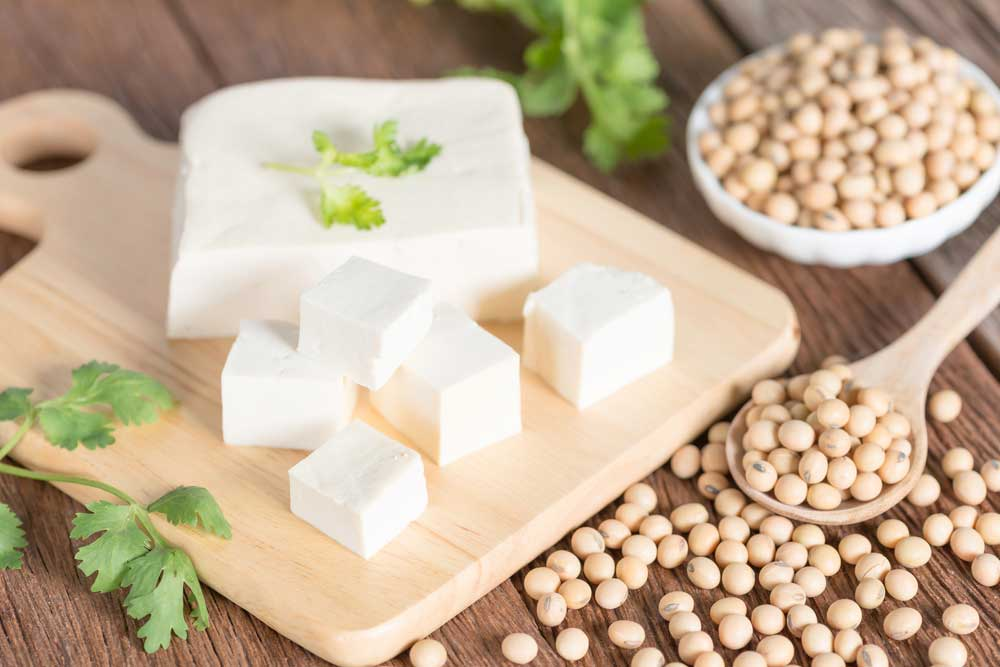 Tofu on a cutting board surrounded by soy beans