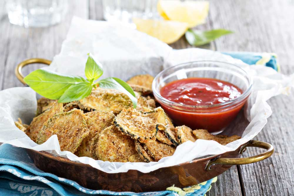 beaded zucchini chips in a paper lined bowl with a small bowl of ketchup