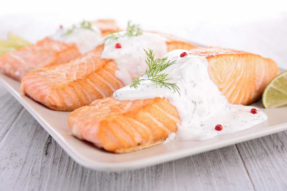 3 salmon filets on a white plate covered in dill sauce.