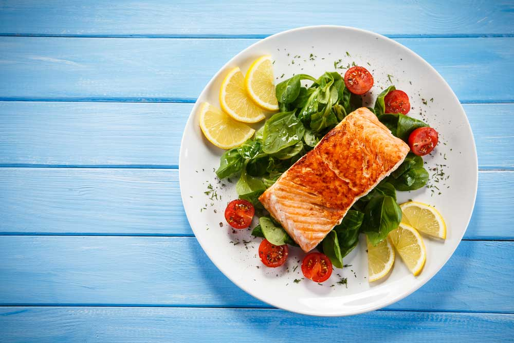 Salmon filet on a bed of greens with tomato and lemon garnish on white plate resting on blue wooden table