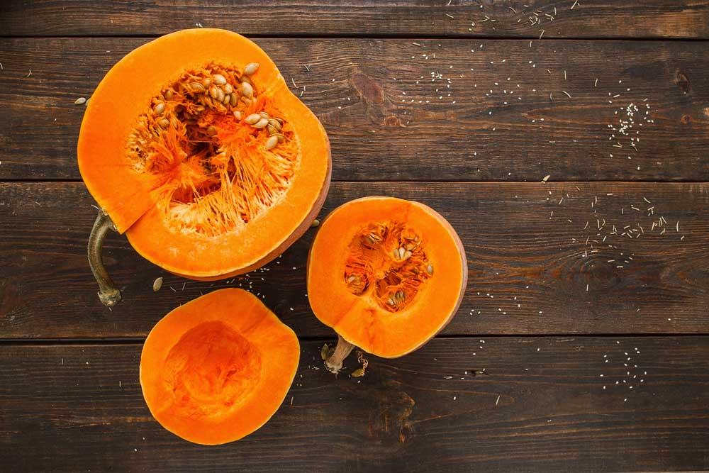 3 pumpkin halves on a wooden table