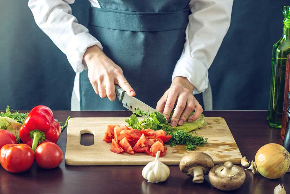 human hands with a knife chopping fresh vegetables