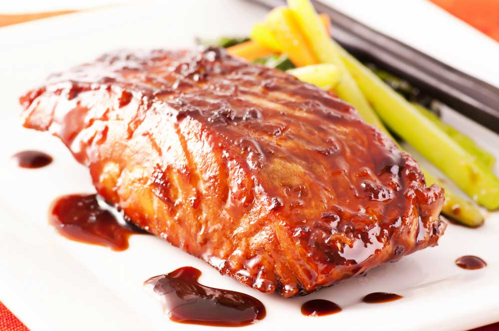 Salmon filet on a white plate with a soy sauce glaze.