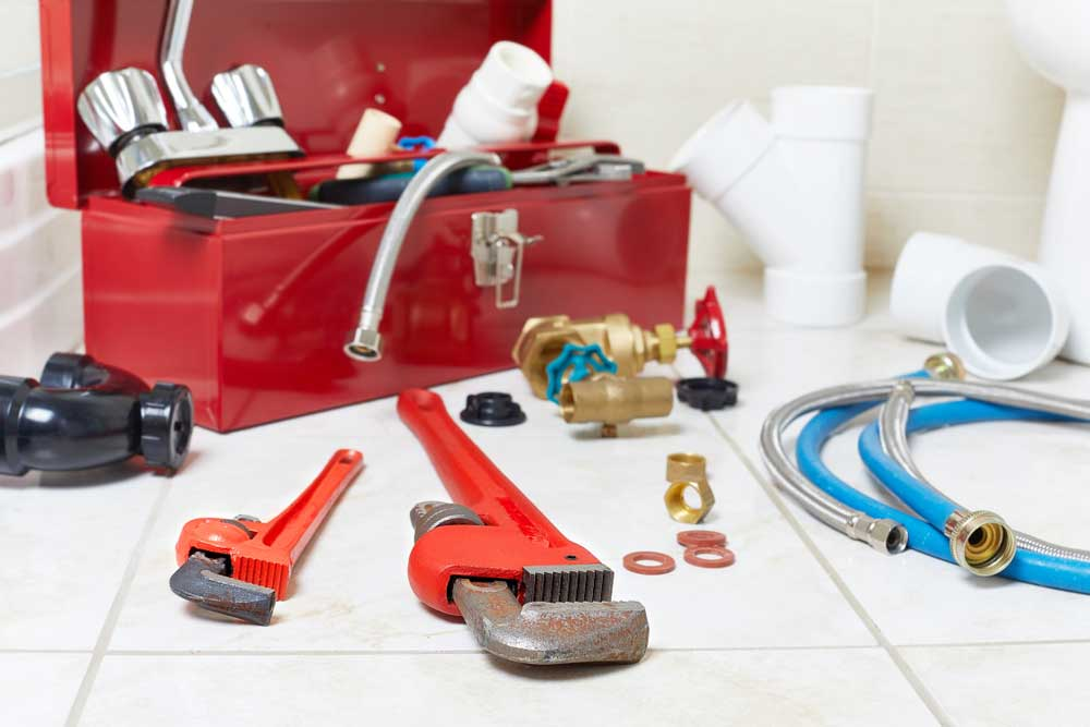 Plumbers toolbox with tools scattered along a  tile floor