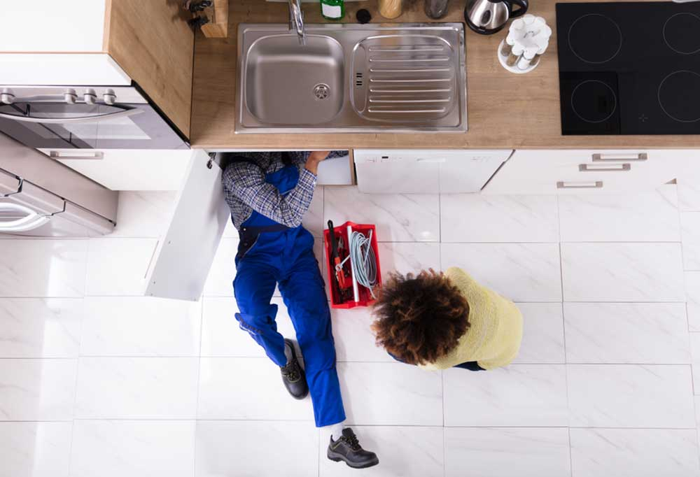 Overhead view of person under sink