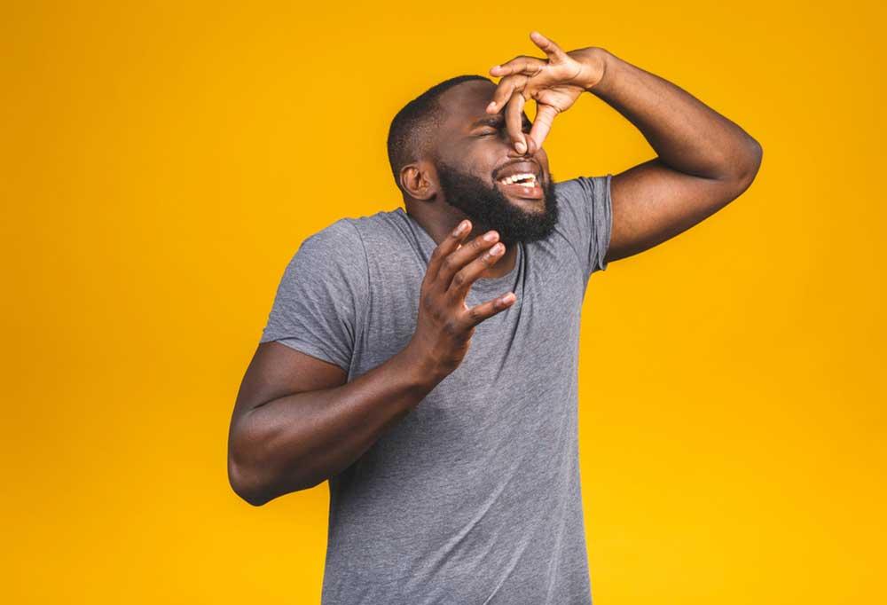 Man on yellow background pinching nose