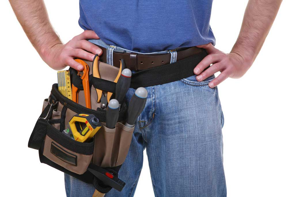 Midsection view of man wearing plumbers tool belt