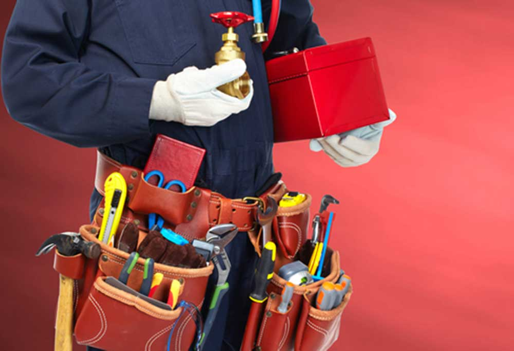 Midsection view of a plumber with tool box and tool belt full of tools.