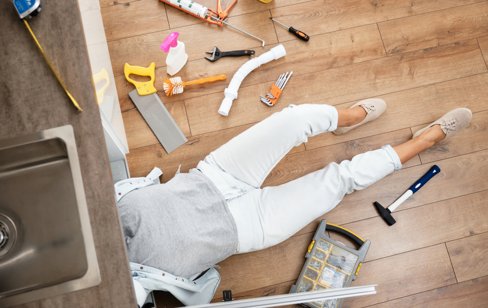 persons torso and legs sticking out from under sink with tools scattered