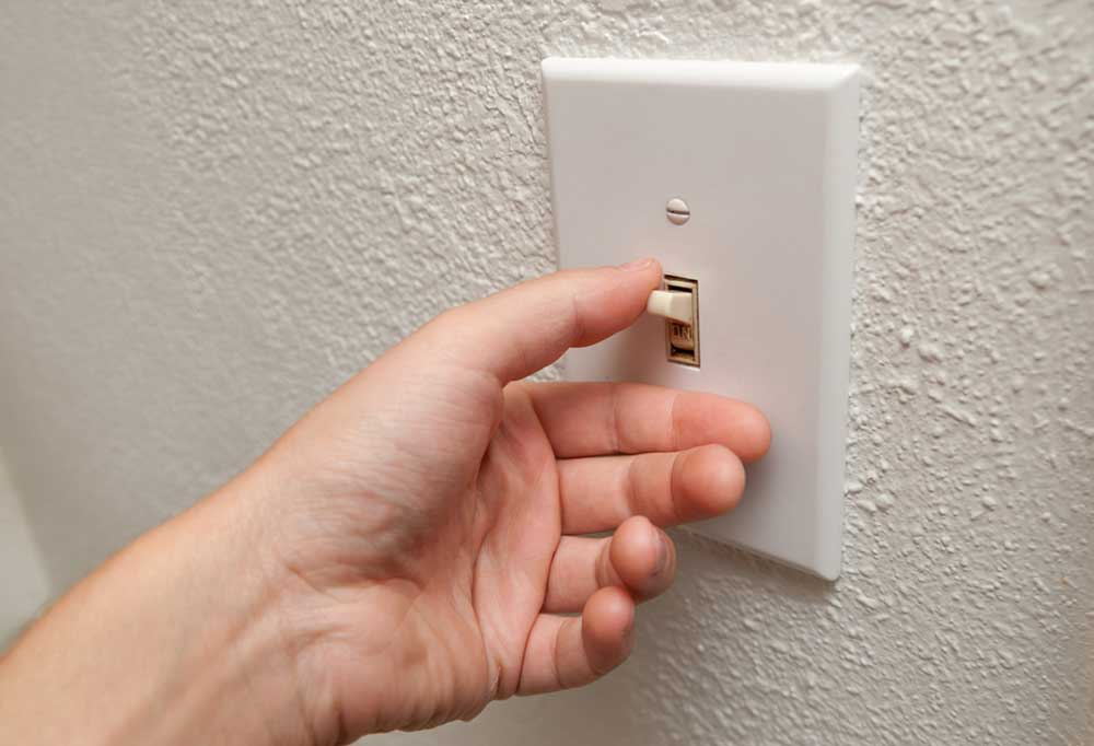 Hand flipping off electrical switch