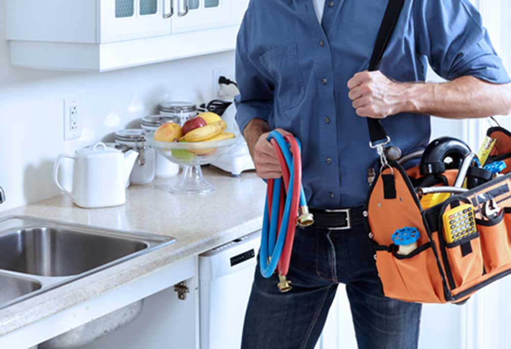 Plumber holding tool bag ad hoses next to kitchen sink