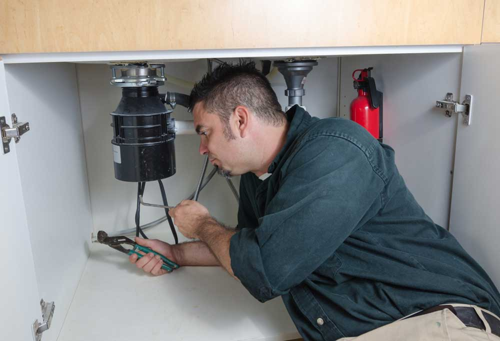 man under sink with pliers fixing garbage disposal