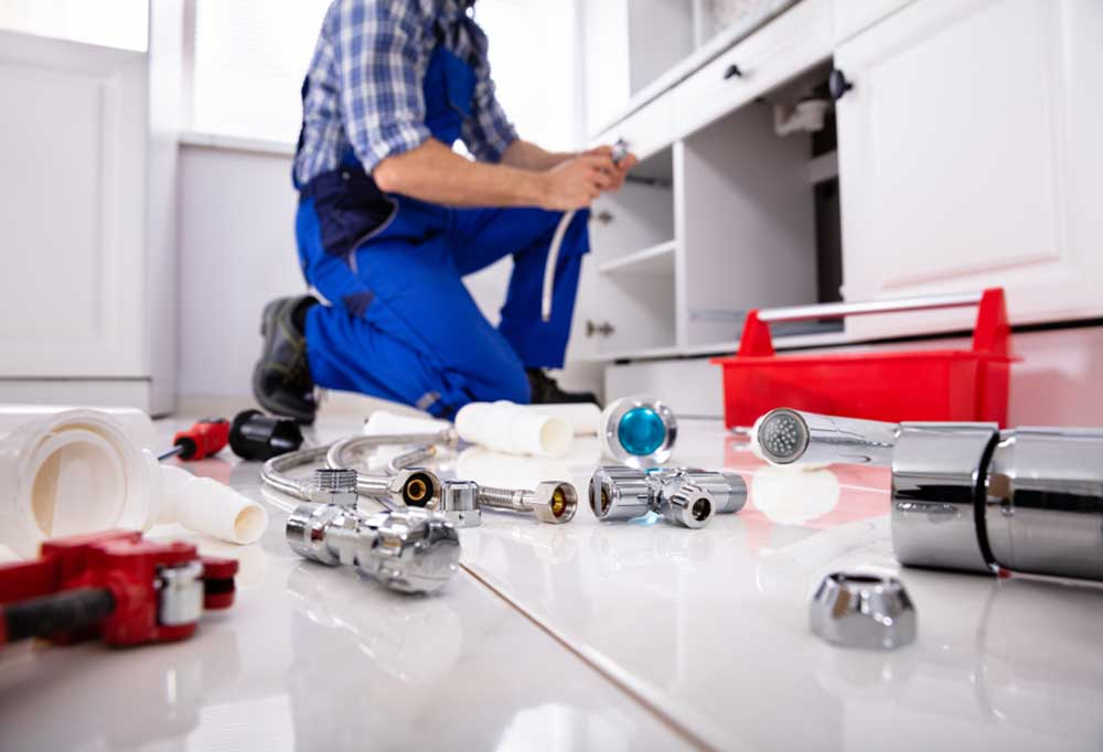 person in overalls with parts and tools scattered across kitchen floor