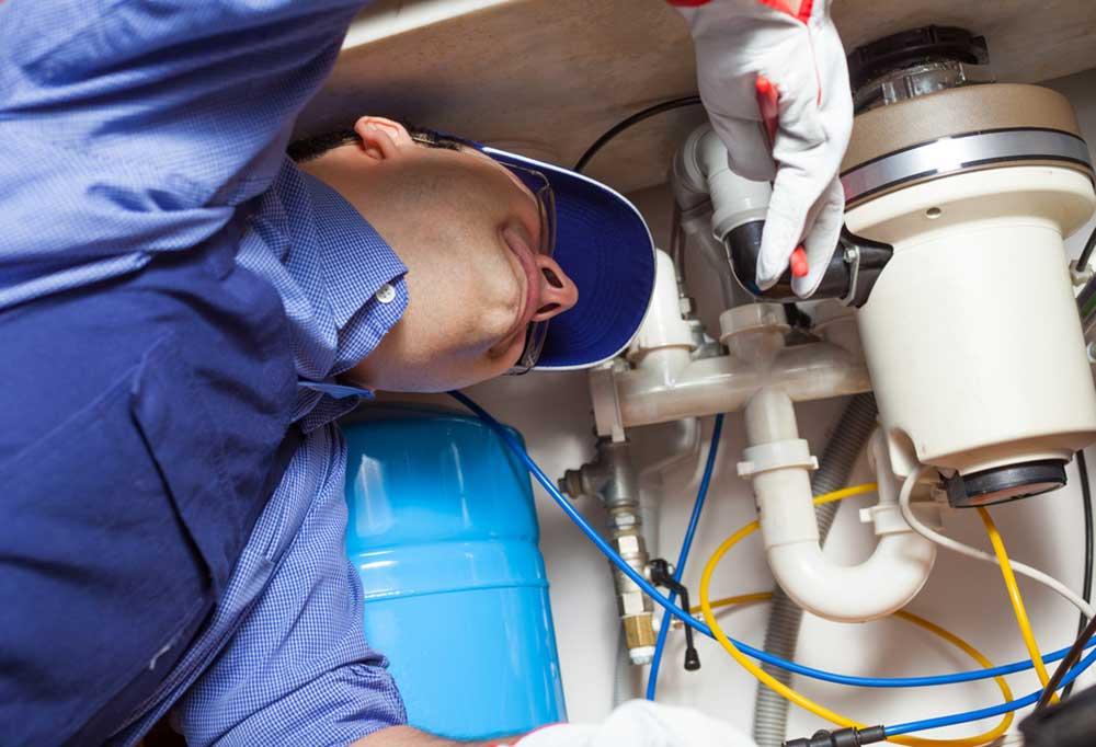 man under sink fixing garbage disposal