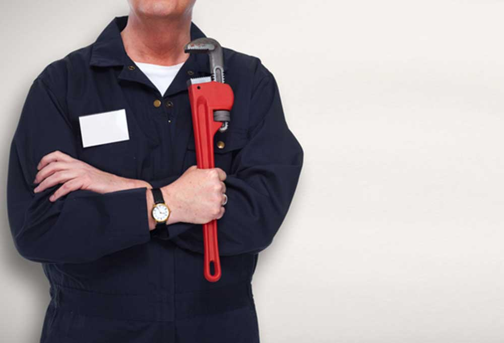 Torso view of plumber holding pipe wrench