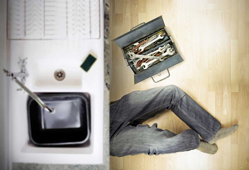 a pair of legs in jeans sticking out from under kitchen sink with a tool box next to them.