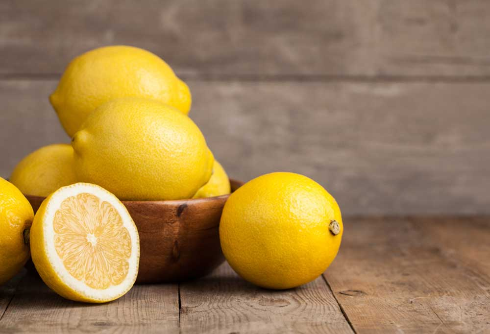 Lemons in a wooden bowl on a wooden table