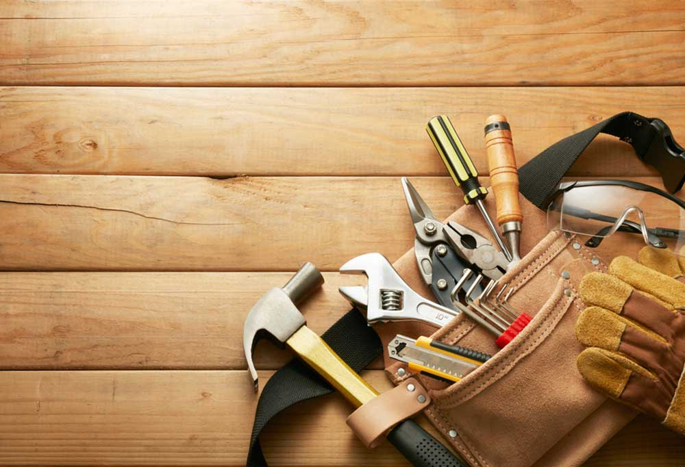 Tools in a tool bag on a wooden surface