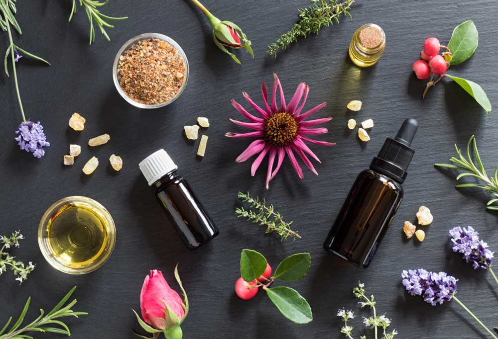 flowers and essential oil bottles scattered on a black slate