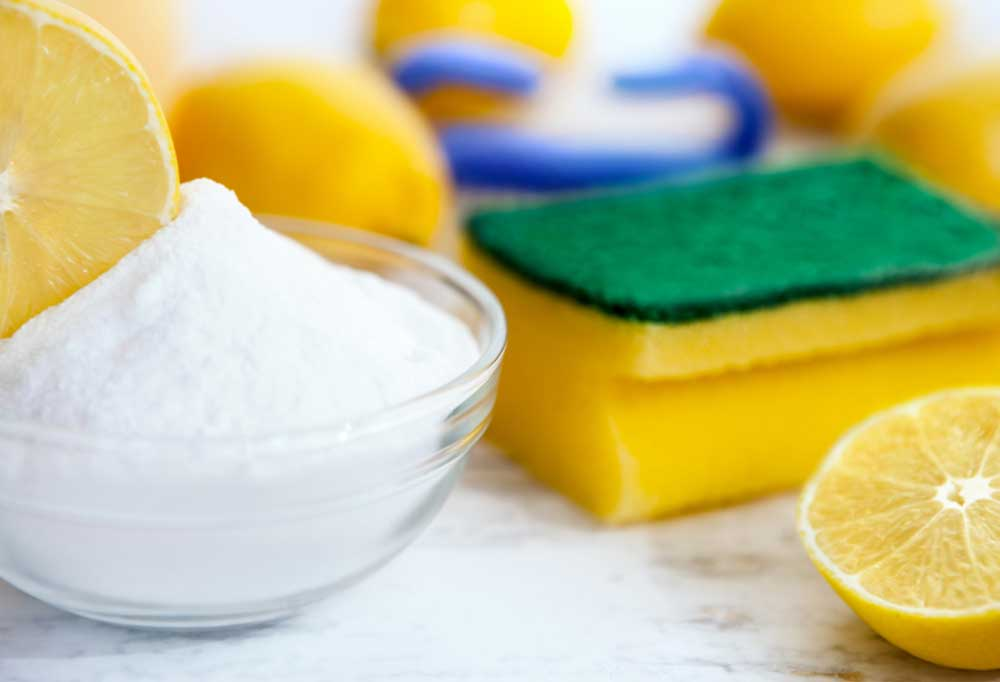 bowl of baking soda with cut lemons and sponges
