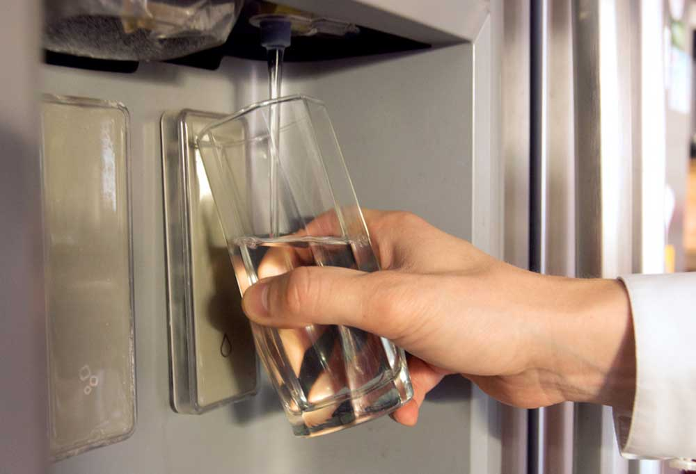 Hand holding a glass  drawing water from a refrigerator door water dispenser