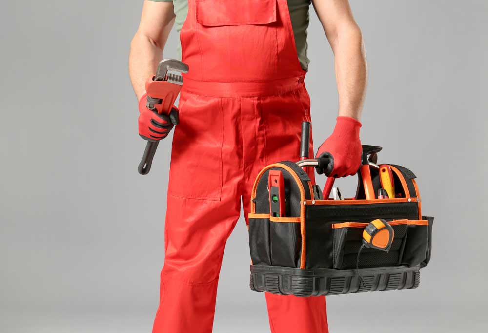 man in bright red overalls holding a pipe wrench in one hand and a tool bag in the other