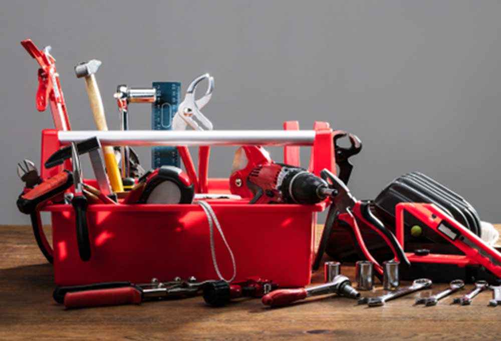 red toolbox with tools on a wooden table