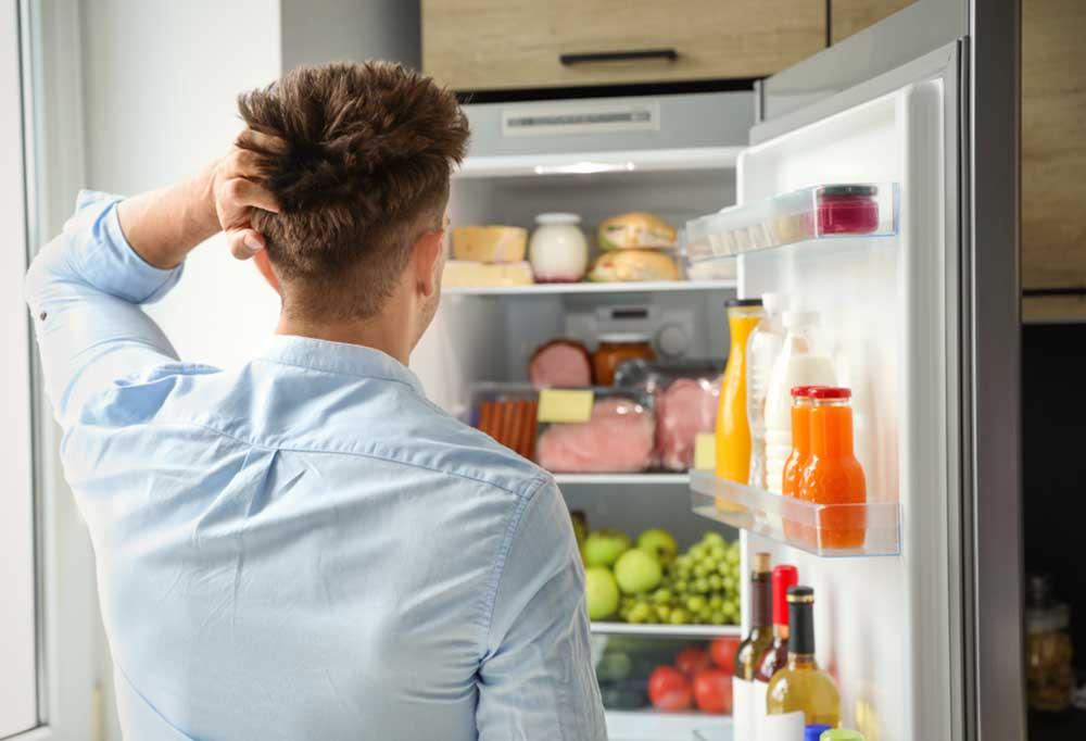 Man rubbing his head, staring into an open fridge