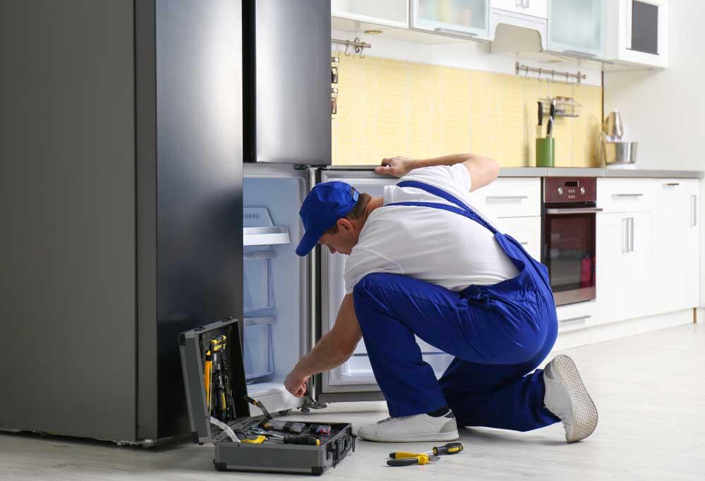 Repair man in blue overalls using a screwdriver on a fridge door
