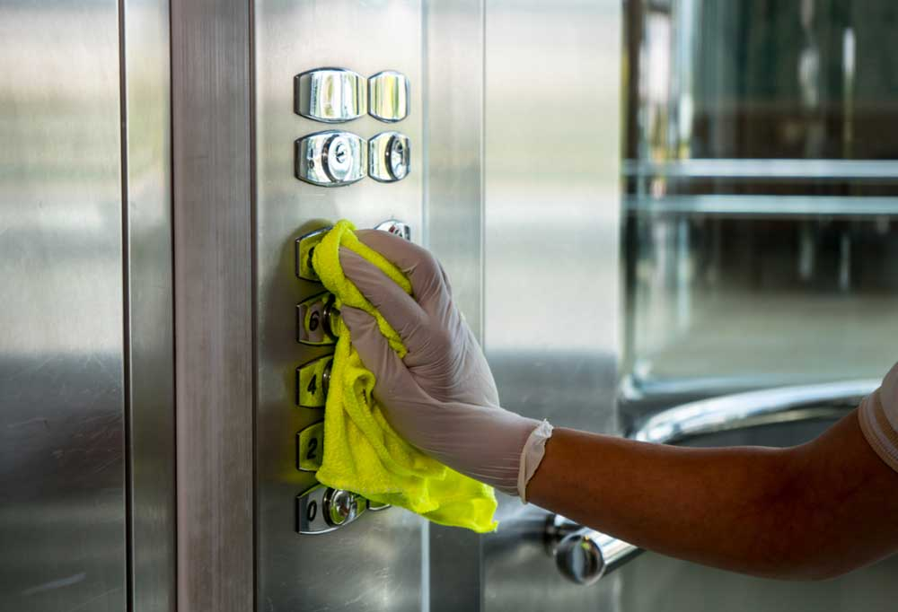 person with gloved hand cleaning elevator buttons with a yellow cloth