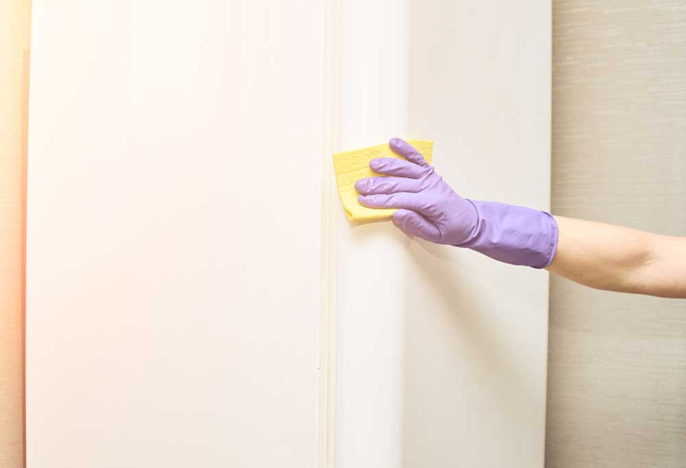 Hand in a purple glove holding a yellow sponge cleaning the outside of a refrigerator