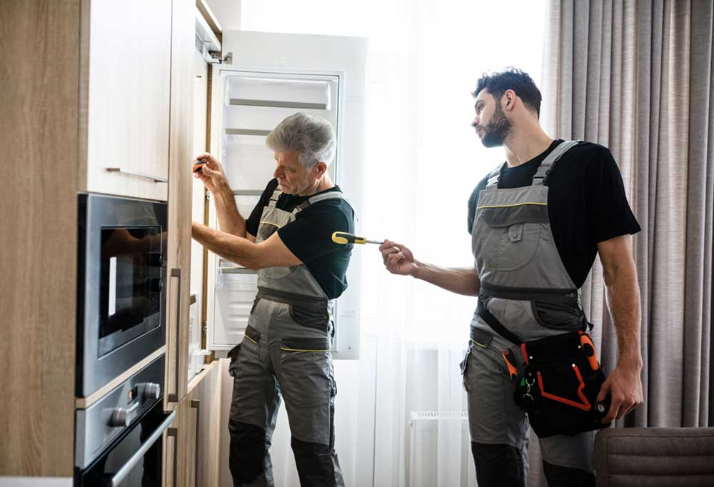 2 men in coveralls with tools fixing a refrigerator