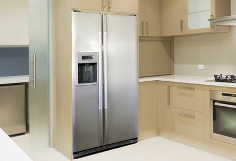 stainless steel fridge in a tan themed kitchen